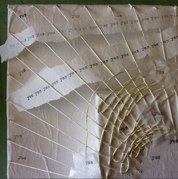 weaving typed-on paper strips through the stitches