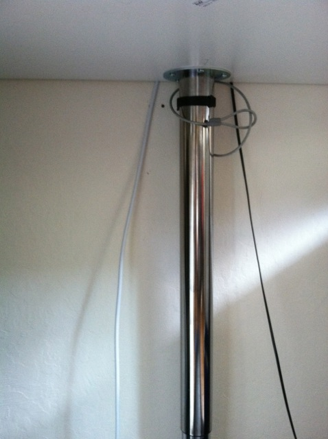 Velcro strip wrapped around GERTON leg and big, fat eye bolt screwed into wall stud.