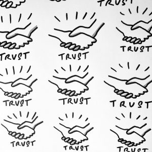 "Doodle icon: Trust [multiple instances of a doodle of two hands shaking, with energy rays extending out from them, with the word ""trust"" underneath each doodle]"
